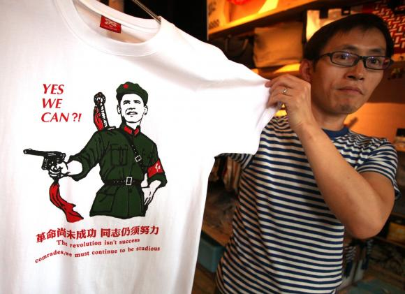 A Chinese shopkeeper shows the latest t-shirt featuring U.S. President Barack Obama in Beijing
