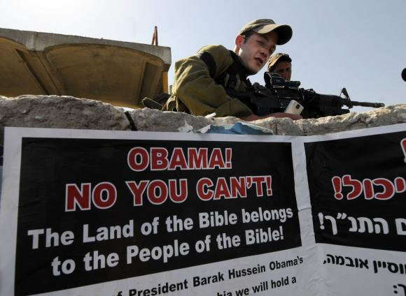 """Israeli soldiers stand near a poster reading """"Obama! No You Can't!"""" in the West Bank - West Bank Set"""