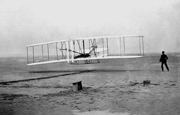 Orville Wright pilots the first flight as brother Wilbur runs alongside at