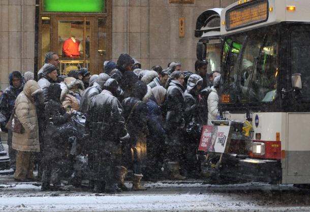 Pedestrians wait for bus in snow storm in Chicago